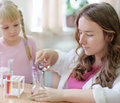 Eldest schoolgirl shows Chemical experience for little girl Royalty Free Stock Photo