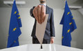 Election or referendum in European Union. Voter holds envelope in hand above ballot. EU flags in background