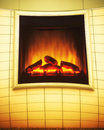 Electric artificial fireplace with orange fire flame interior ad closeup of as advertise billboard on wall Stock Image