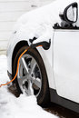Electric car charging plugged in to an outlet recharging outdoors in winter snow Royalty Free Stock Photo