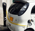 Electric car is charging white being charged at a station on pavement Royalty Free Stock Photos