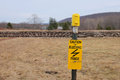 Electric fence typically used for livestock and horses is shown with bright yellow sign warning of shock danger Stock Photo