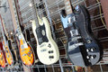 Electric guitars group of shiny hanging on a wall and for sale photographed on an angle Royalty Free Stock Images