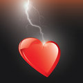 Electric heart red hit by lightning isolated against a black background Stock Photography