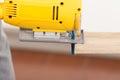 Electric jigsaw tool cutting wood close up Stock Photos