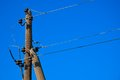 Electric pole old wooden against a blue cloudless sky Royalty Free Stock Photography