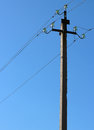 Electric pole with wires and insulators against blue sky Royalty Free Stock Photo