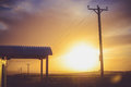 Electric Post and Waiting Shed During Sunset