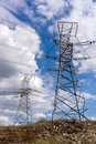 Electric power high voltage transmission line pylon tower on blue sky and white cloud background. Royalty Free Stock Photo