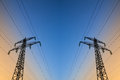 Electric power lines against blue sky Stock Photography