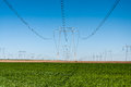 Electric power lines on green crop field high energy Royalty Free Stock Photo