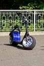 Electric scooter with wide wheels stands on the asphalt in the park Royalty Free Stock Photo