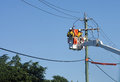 Electric utility workers two repairmen working on power lines from a bucket truck Royalty Free Stock Photos