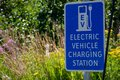 Electric vehicle only charging station sign for environmentally friendly vehicles with a green grass and flower background Royalty Free Stock Photo