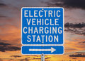 Electric vehicle charging station sign with sunset sky isolated Royalty Free Stock Image