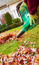 Electrical blower cleaning leaves from front yard during autumn vertical photo of gloved hands holding with house in background Stock Images