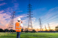 Electrical engineer with high voltage electricity pylon at sunrise background Royalty Free Stock Photo