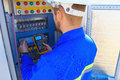 Electrical engineer with a multimeter performs adjustment work in the blurred control cabinet