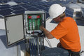 Electrical engineer repairing electricity box at solar power plant Stock Photos