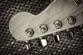 Electrical guitar headstock closeup with vignette and textured background top view Stock Photos