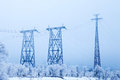 Electrical high-voltage metal pillars in winter Royalty Free Stock Photo