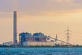 Electrical power plant near the sea with sunset light Royalty Free Stock Photos