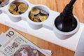 Electrical power strip with connected plug and polish currency money energy costs on wooden floor board concept of saving on Stock Photography
