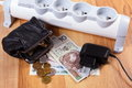 Electrical power strip with disconnected plug and polish currency money energy costs black leather pocket purse concept of saving Royalty Free Stock Image