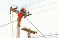 An electrical power utility worker in a bucket fixes the line Stock Image
