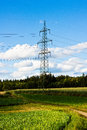 Electrical tower with power lines in a field under a blue sky. Royalty Free Stock Photo