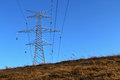 Electrical tower and wires overhead metal structure of an electric pylons with high tension passing with brown dead grass hill in Stock Photography