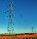 Electrical towers and high tension cables series of electric pylons wires stretching into the horizon against a clear blue sky in Stock Photos