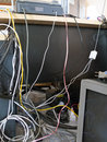 Electrical wires and cables in a mess multiple that connecting from office equipment on working table Stock Photography