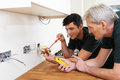 Electrician With Apprentice Working In New Home Royalty Free Stock Photo