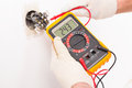 Electrician checking socket voltage with digital multimeter Royalty Free Stock Photos
