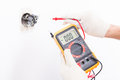 Electrician checking socket voltage with digital multimeter Royalty Free Stock Photo