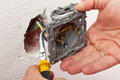 Electrician hand mounting a wall fixture Royalty Free Stock Photo