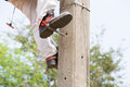 Electrician lineman repairman worker at climbing work on electric post power pole Royalty Free Stock Photo