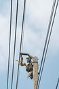 Electrician maintenance and install the power cord on the high pole Royalty Free Stock Image
