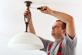 Electrician mounting ceiling lamp installing the wires mask Stock Photos
