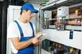 Electrician worker inspecting young adult builder engineer electric counter equipment in distribution fuse box Stock Photo