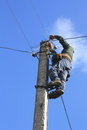 Electrician working on electric power pole against the blue sky Royalty Free Stock Photo