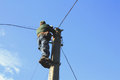Electrician working on electric power pole against the blue sky Royalty Free Stock Images