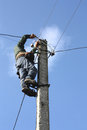 Electrician working on electric power pole against the blue sky Stock Images