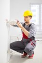 Electrician working with wires in new apartment Stock Image