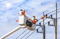Electricians repairing wire of the power line with bucket hydraulic lifting platform Royalty Free Stock Photo