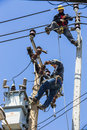 Electricians working on the electricity pole bangkok thailand may to replace electrical insulator while another one watching Stock Photography