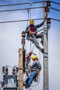 Electricians working together bangkok thailand may to replace the electrical insulator on the electricity pole Royalty Free Stock Image