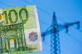Electricity costs hundred euro banknote infront of an out of focus power pole as a concept for Royalty Free Stock Photography