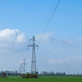 The electricity high voltage pylons with wires on background of autumn sky in a field Stock Images